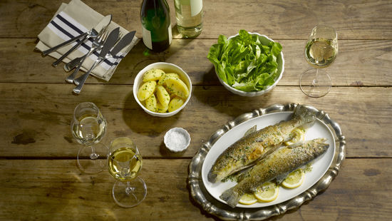 The picture shows fried trout with salt potatoes and a glass of white wine.