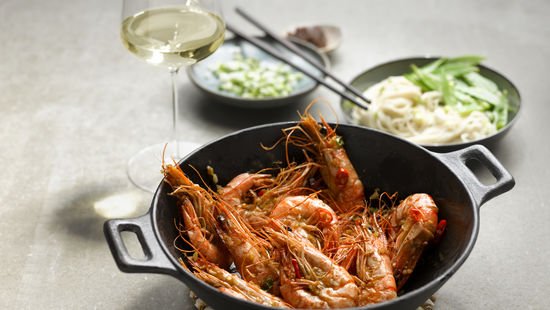 The picture shows Spicy Prawns and a glass of white wine.