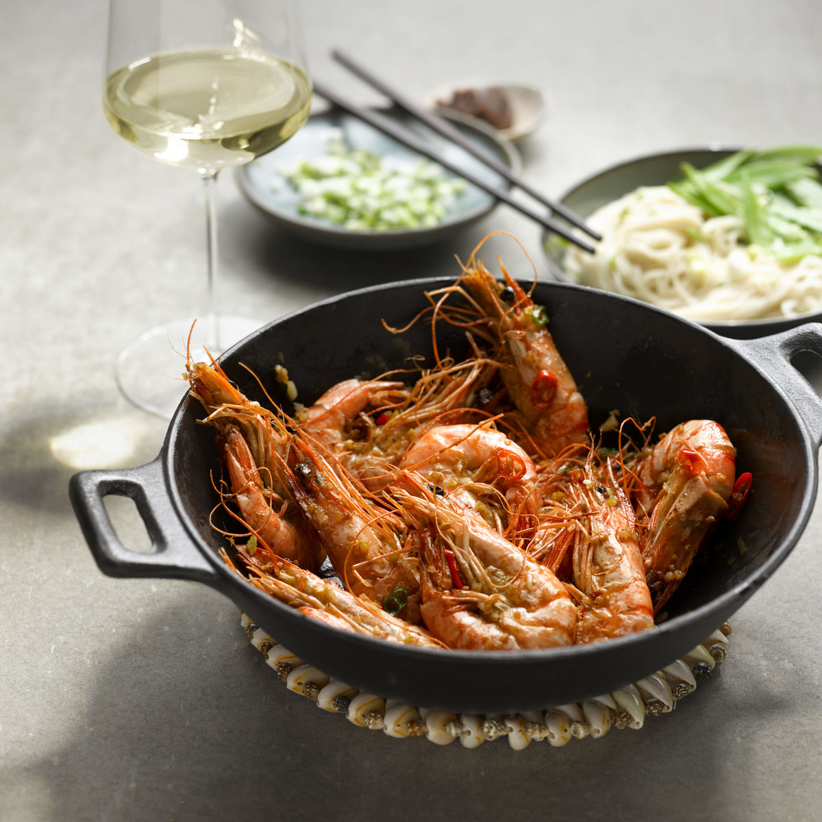 The picture shows the dish spicy prawns and a glass of white wine.