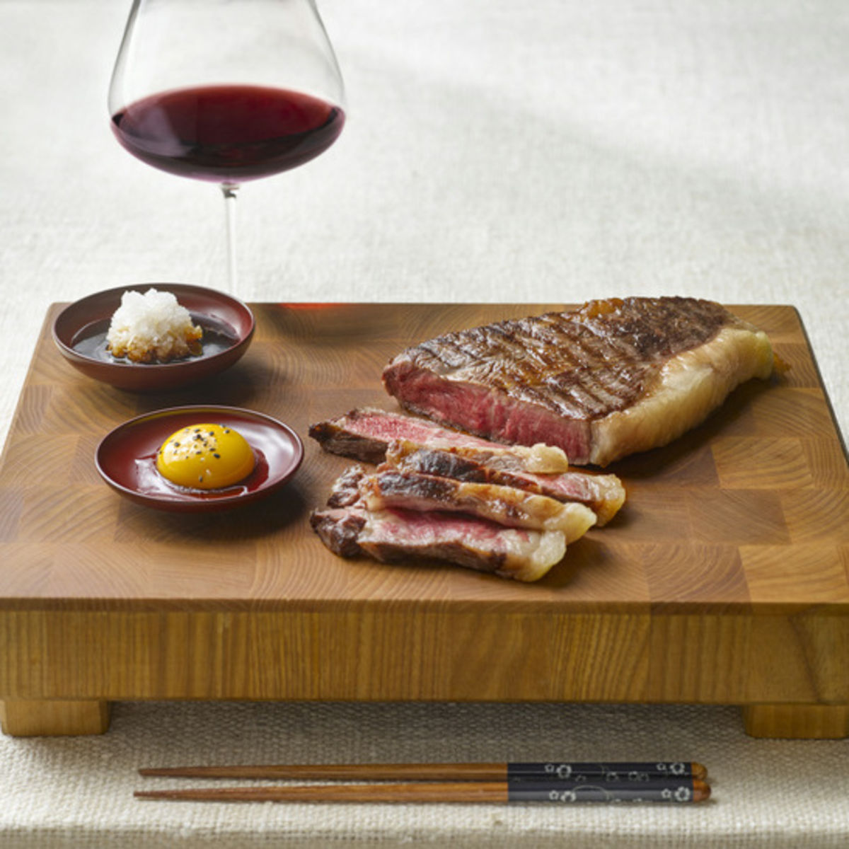 The picture shows wagyu beef and a glass of red wine,