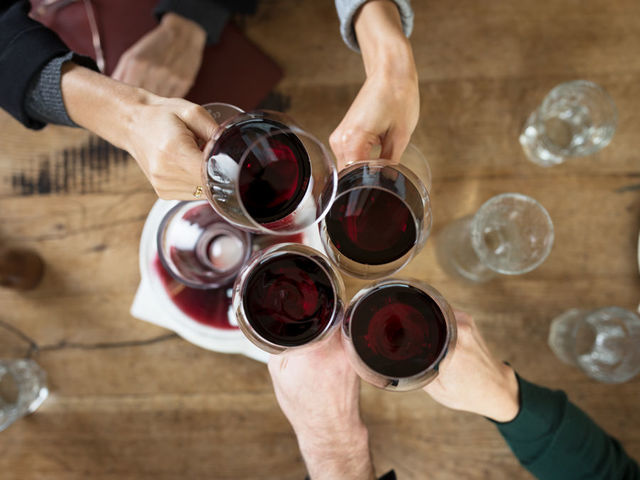 A picture shows four people toasting with red wine.