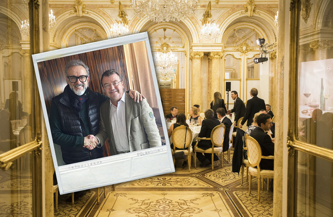A picture shows Massimo Bottura together with Willi Klinger in the foreground and a scene from the SALON gala dinner in the background, © AWMB.