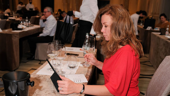 A picture shows a woman tasting wine in Russia and being connected with winegrowers in Austria via an online app.