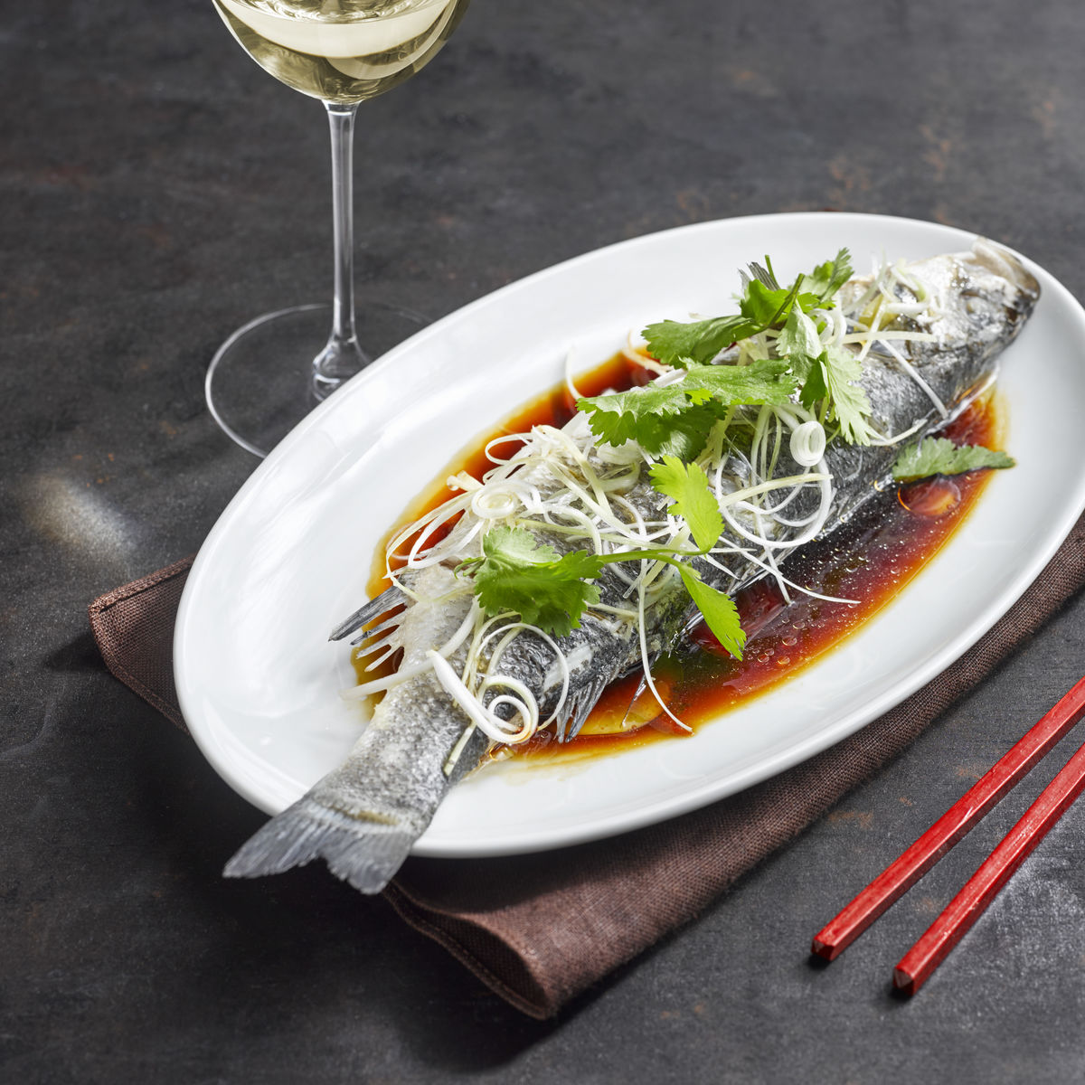 The picture shows the dish steamed fish and a glass of white wine.