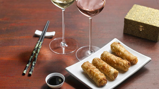The picture shows fried spring rolls and two glasses of wine, filled with white wine and rosé.