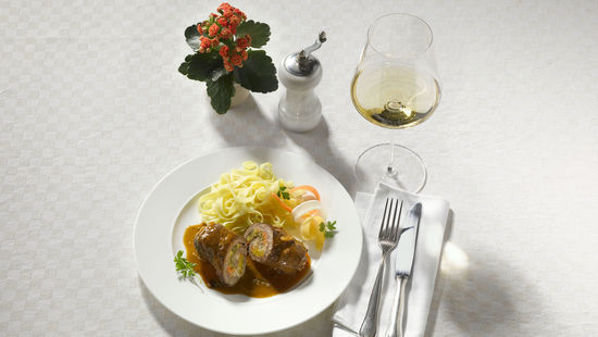 The picture shows beef rolls on a plate and a glass of white wine.