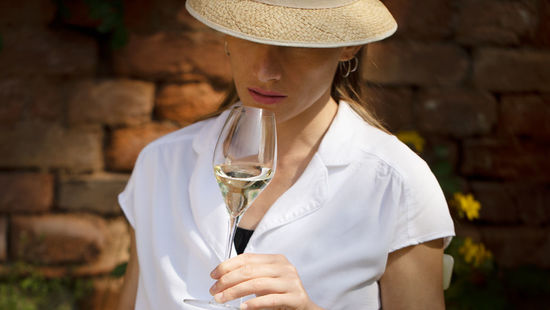 A woman with a hat is drinking Austrian sparkling wine
