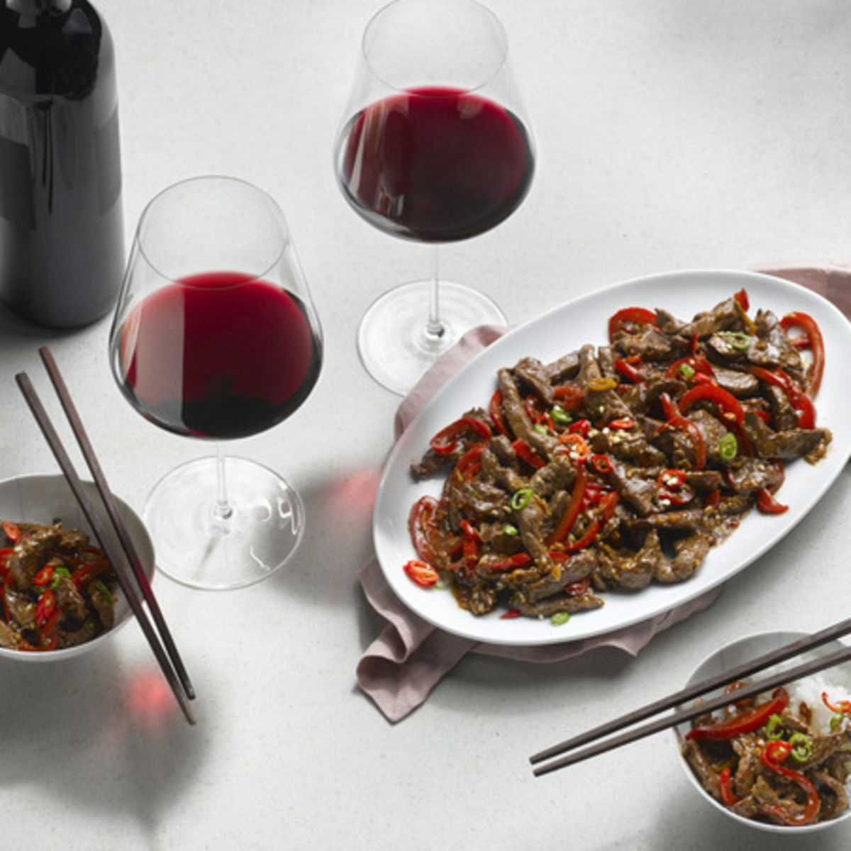 The picture shows the dish sichuan meat and two glasses of red wine.