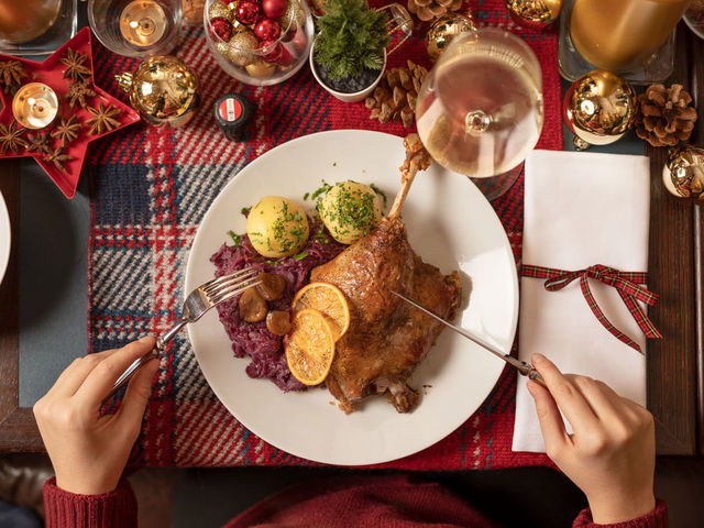 A picture shows a plate of christmas goose witha a glass of Austrian white wine.