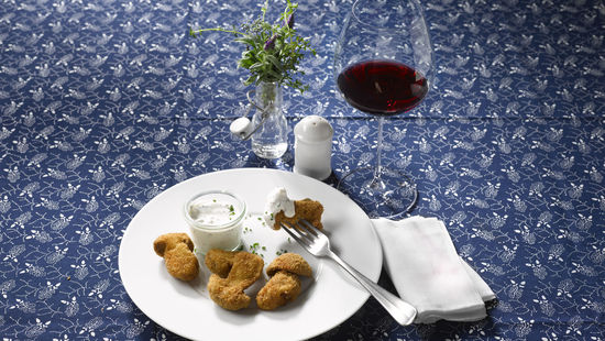 The picture shows fried porcini and a glass of red wine.