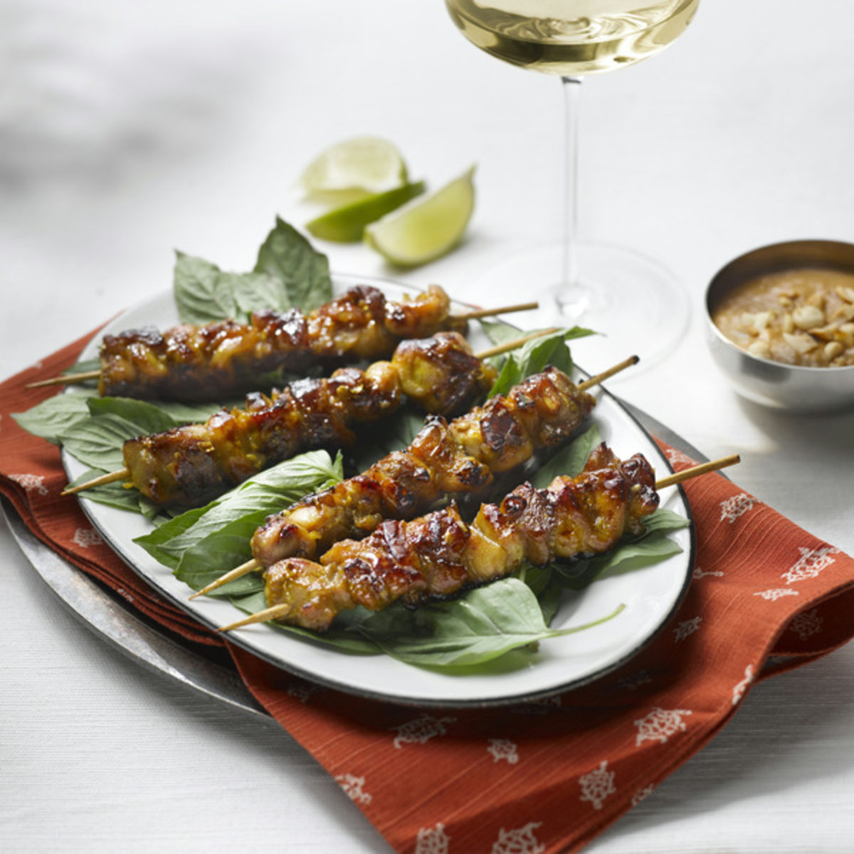 The picture shows chicken skewers with peanut sauce and a glass of white wine.