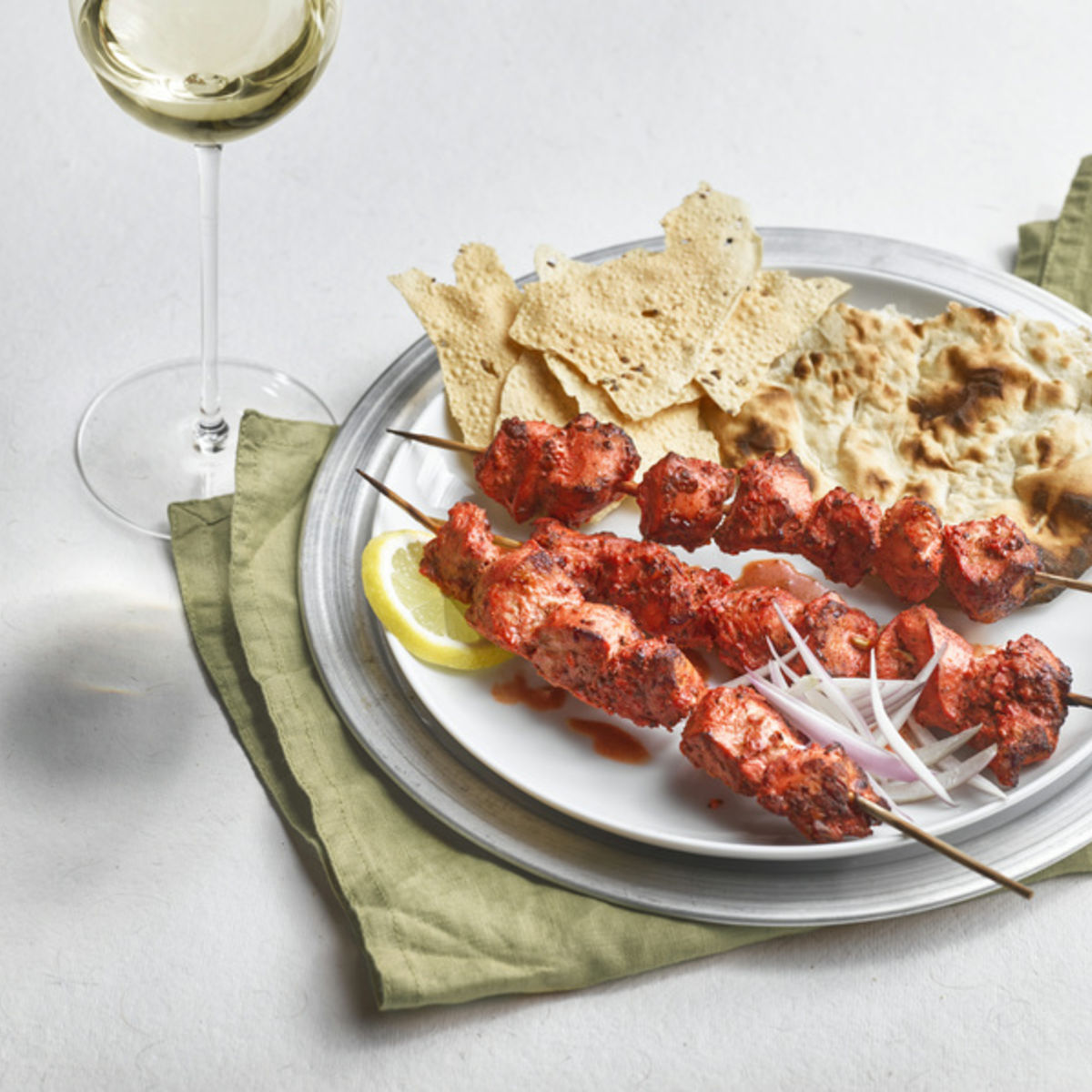The picture shows Tandoori Chicken and a glass of white wine.