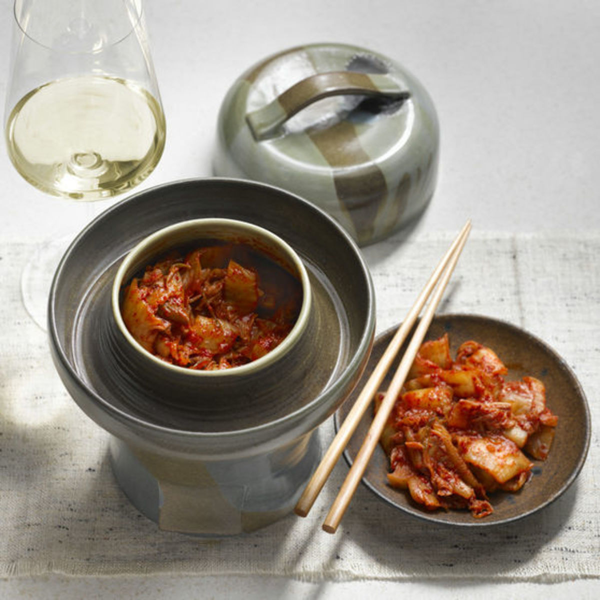 The picture shows the dish Kimchi and a glass of red wine.