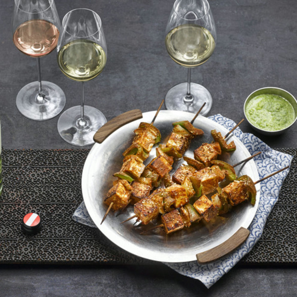 The picture shows the vegetarian dish Paneer Tikka and thre glasses, filled with white and rosé wine.