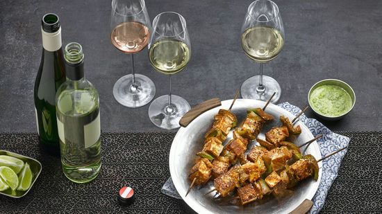The picture shows the dish Paneer Tikka and three glasses, filled with white and rosé wine.