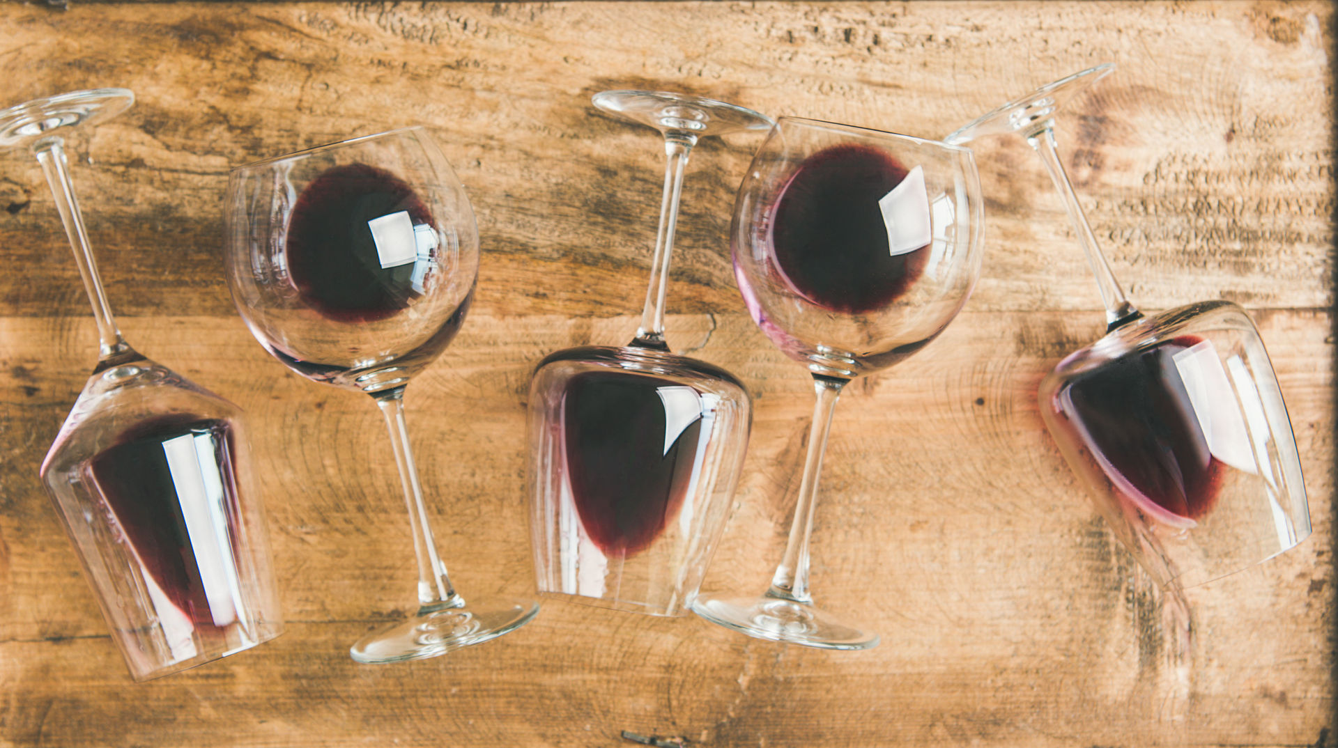 A picture shows glasses of red wine lying on a wooden plate.