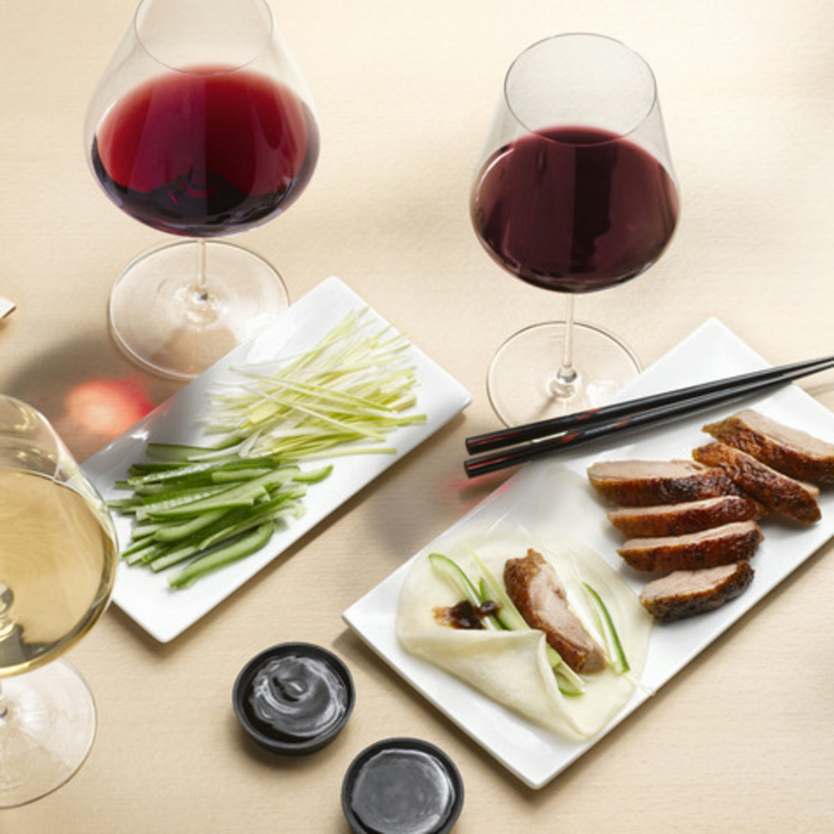 The picture shows the dish peking duck and three glasses, filled with white and red wine.