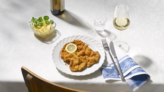 The picture shows Wiener Schnitzel with potatoes and a glass of white wine.