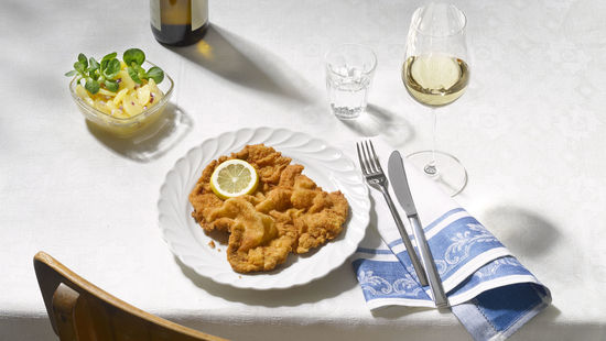 The picture shows a Wiener Schnitzel with potatoe salad and a glass of white wine.