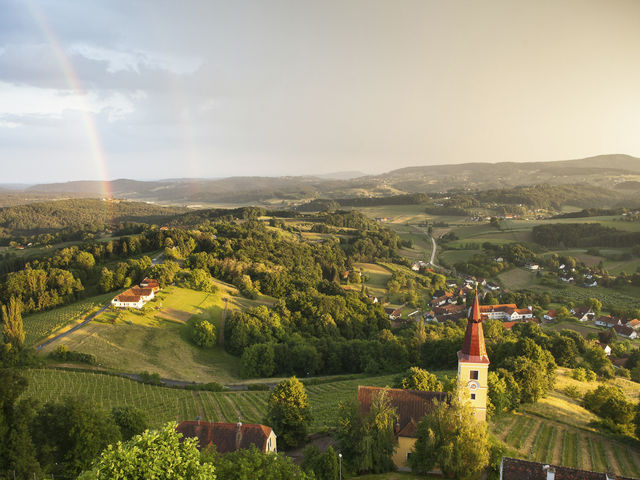 The picture shows a church and a rainbow and the vineyards of the Vulkanland Steiermark.
