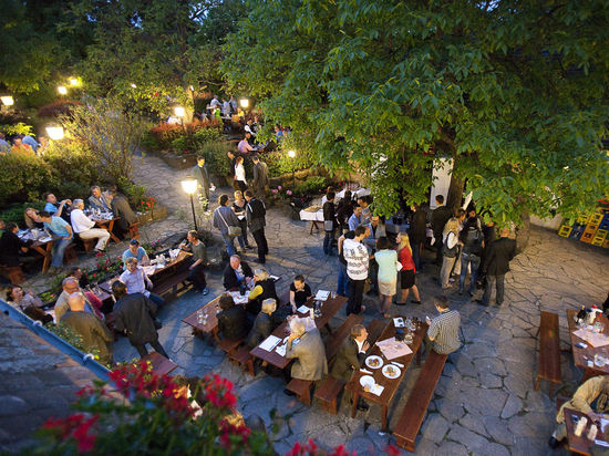 "A picture shows a typical Austrian wine tavern (""Heuriger"") on a warm summer evening."