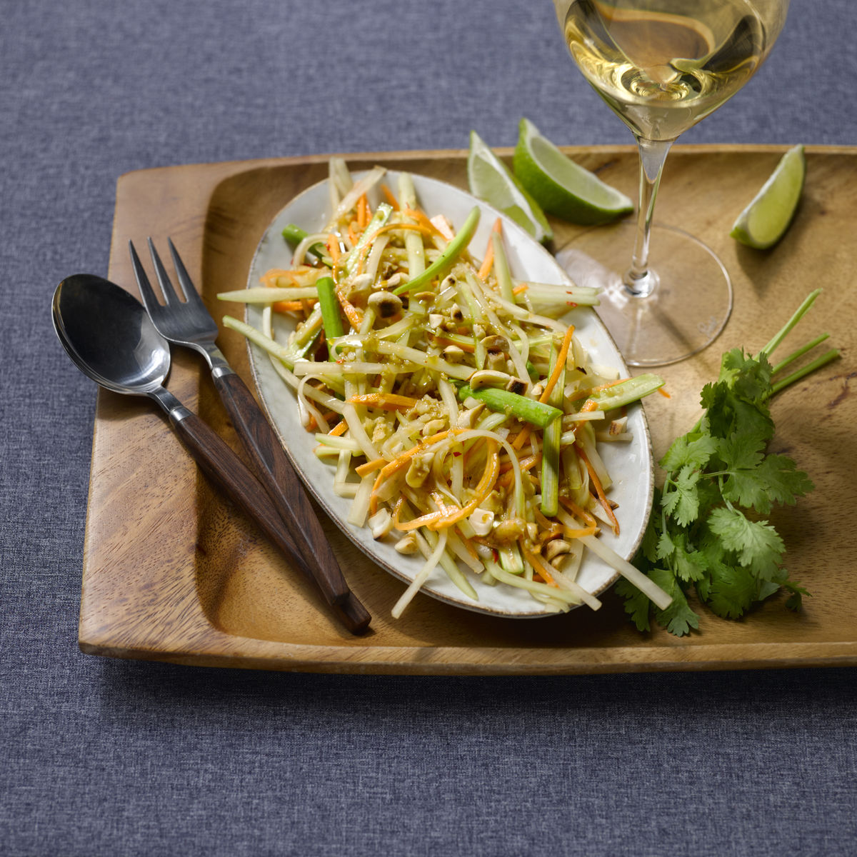 The picture shows the dish Som Tam and a glass of white wine.