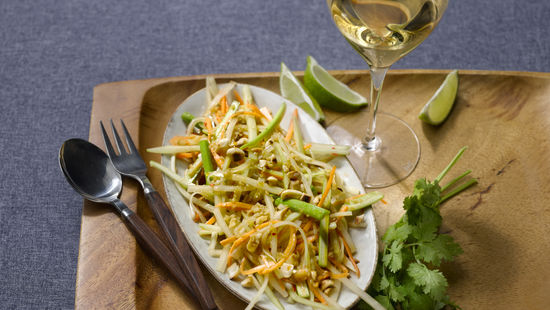 The picture shows the spicy papaya salad Som Tam and a glass of white wine.