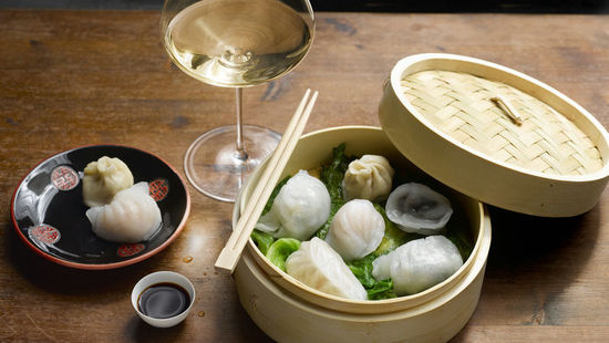 The picture shows the dish Dim Sum on a wooden table and a glass of wine.