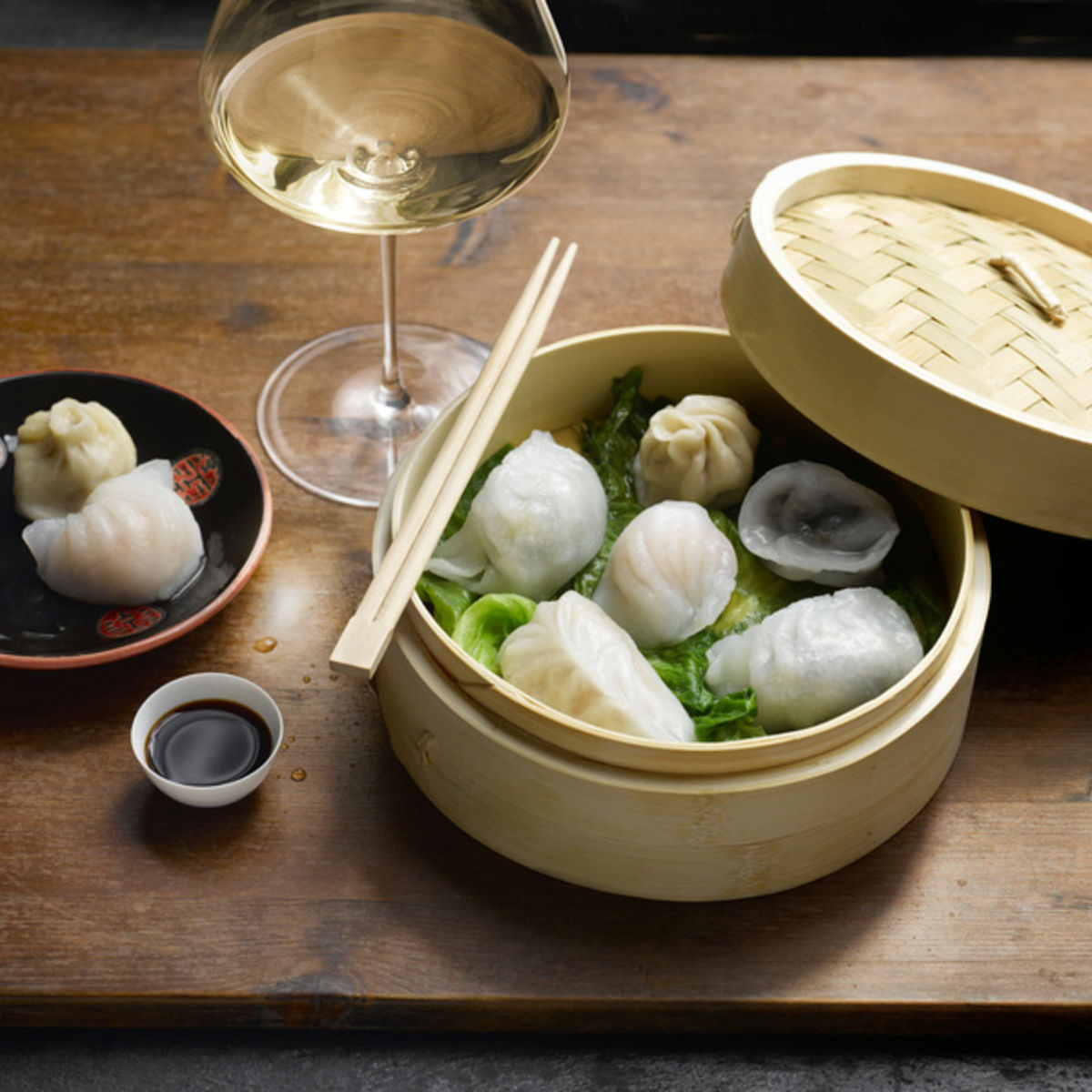 The picture shows steamed dumplings with a glass of white wine.