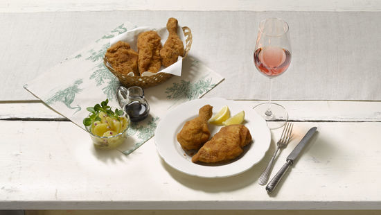 The picture shows breaded fried chicken on a plate with a glass of Rosé wine.