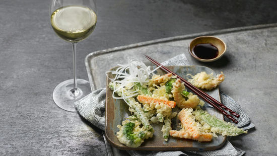 The picture shows the dish Tempura with a glass of wine.