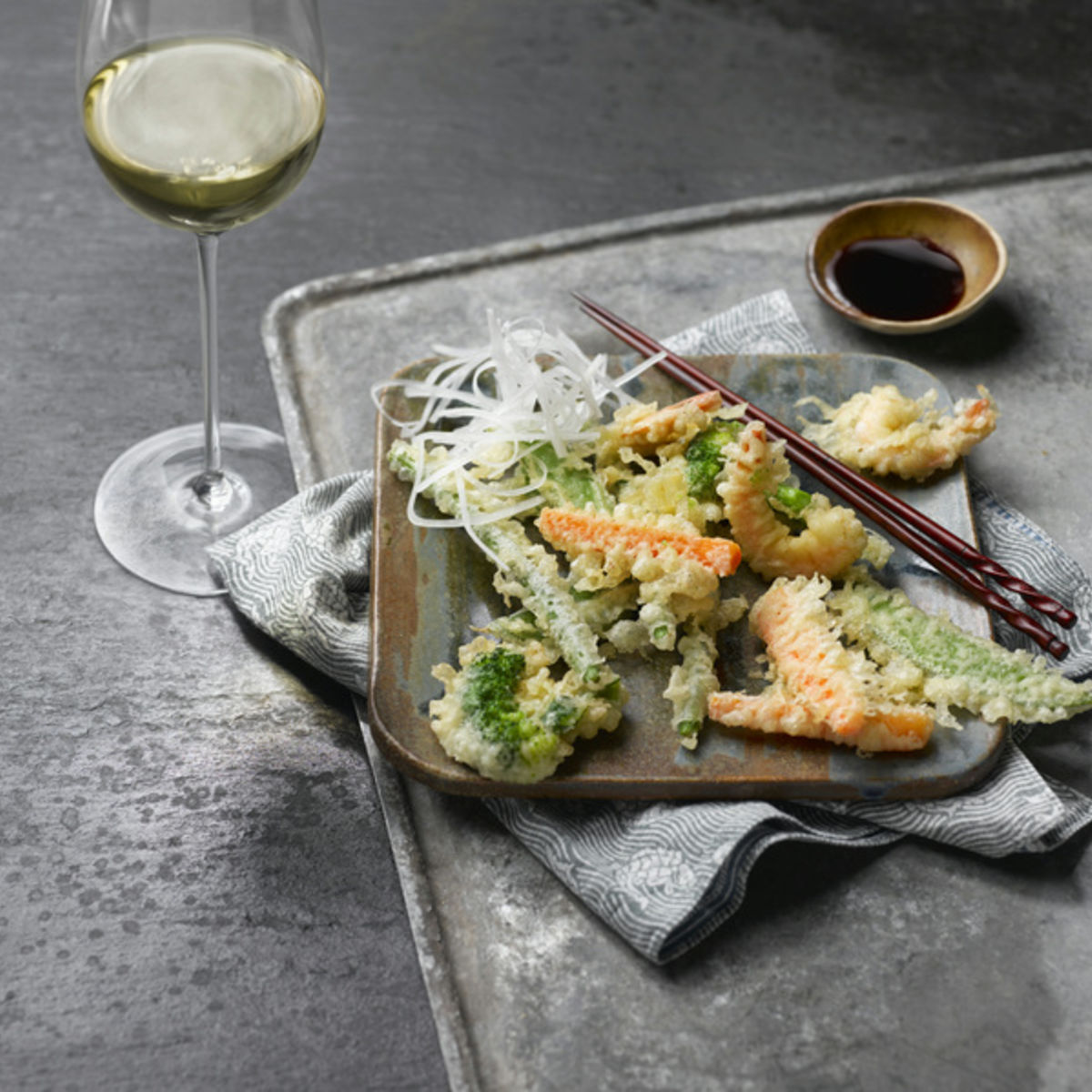 The picture shows fried vegetables with a glass of white wine.