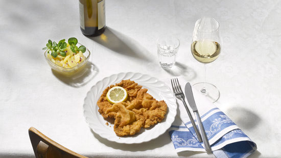 The picture shows Wiener Schnitzel on a plate and a glass of white wine.