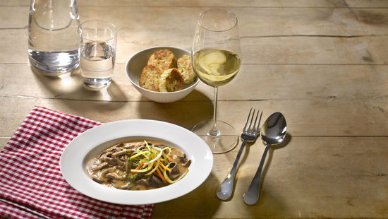 The picture shows the dish Kalbsbeuschel and a glass of white wine on a wooden table.