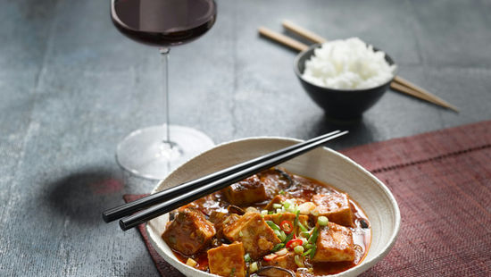 The picture shows the dish mapo tofu and a glass of red wine.