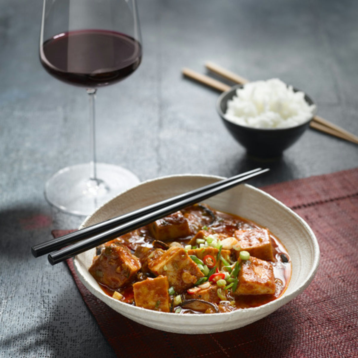 The picture shows the vegan dish Mapo Tofu and a glass of red wine.