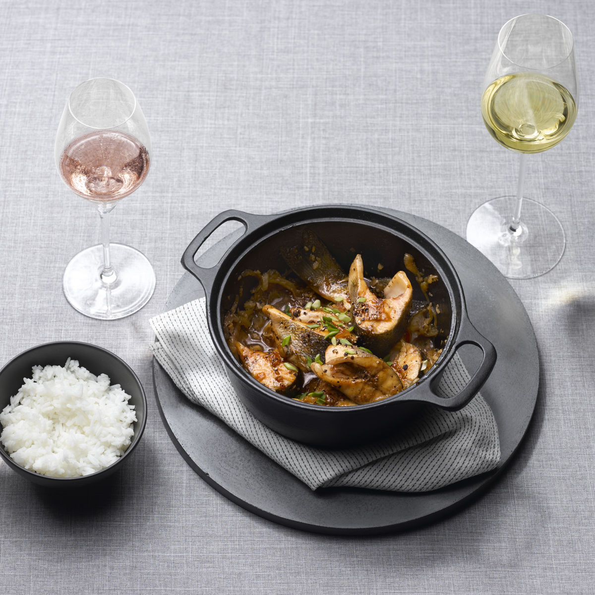 The picture shows the dish Ca Kho To and three glasses, filled with white and rosé wine,