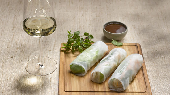 The picture shows Vietnamese Spring Rolls and a glass of white wine.