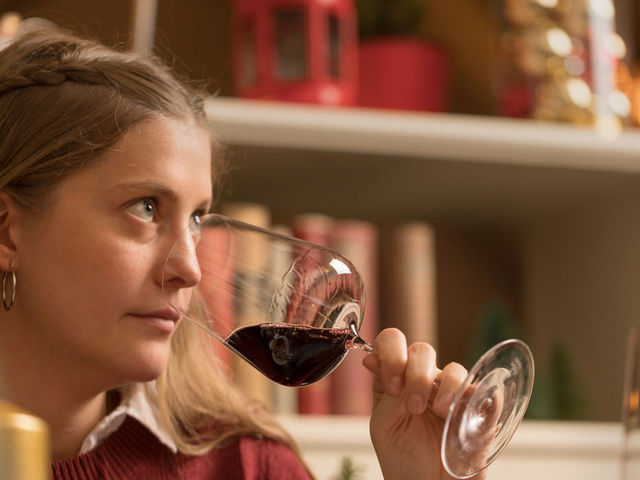 A picture shows a woman smelling a glass of Austrian red wine.